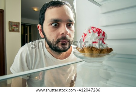 funny man sees the sweet cake in the fridge
