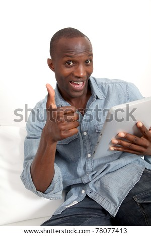 Funny man using electronic tablet at home - stock photo