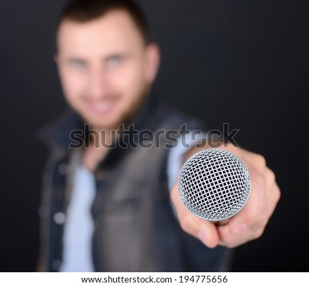 Funny man with microphone singing karaoke isolated on a black background - stock photo