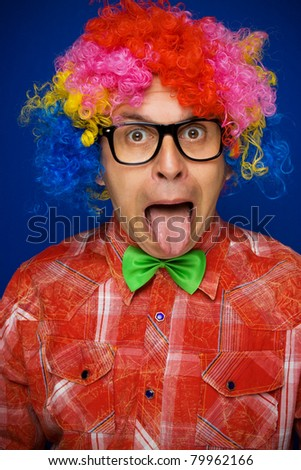 Funny man with multicolor party wig sticking out tongue - stock photo