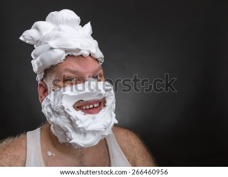 Funny man with shaving foam covered face - stock photo