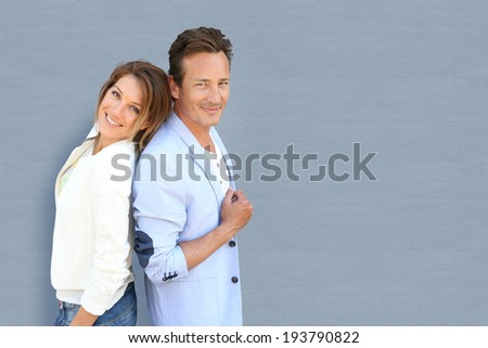 Funny mature couple standing on grey background - stock photo