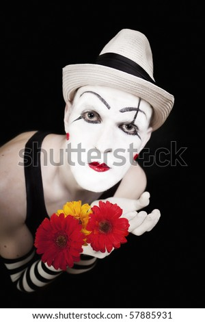 Funny mime in white hat with bouquet of red gerberas on black background - stock photo