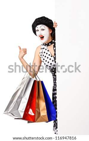 Funny mime woman holding blank billboard and shopping bags. Isolated on white background - stock photo