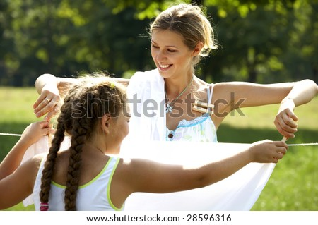 Funny mom and daughter hanging clothes on the line outdoors - stock photo