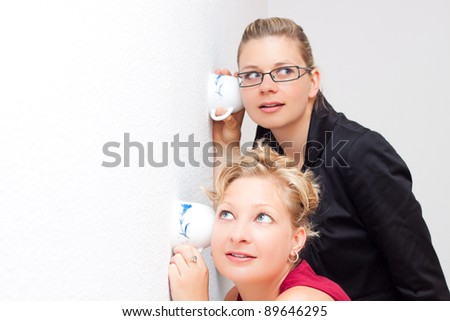Funny moment of two young surprised women listening through the wall. - stock photo