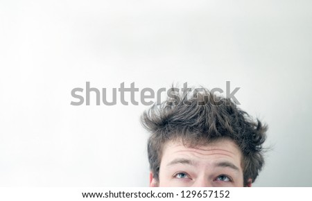 "Funny morning look of a young adult men with on a white (greenish/blueish) background - not ""isolated"". This is also the Hangover or just ""a bad night"" look. You can see a bit of fatigue."