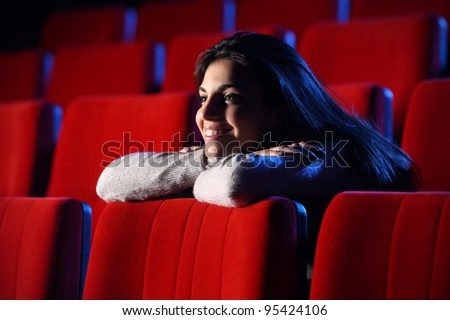 funny movie: portrait of a pretty girl in a movie theater, she leans her elbows on the back row of chairs in front of her, totally relaxed - stock photo
