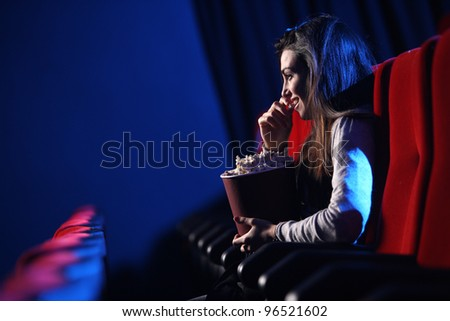 funny movie: portrait of a pretty young woman, she  eats popcorn and smiles - stock photo