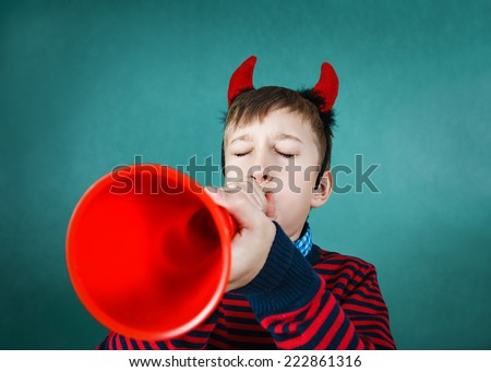 Funny naughty child with Devil's costume playing red pipe - stock photo