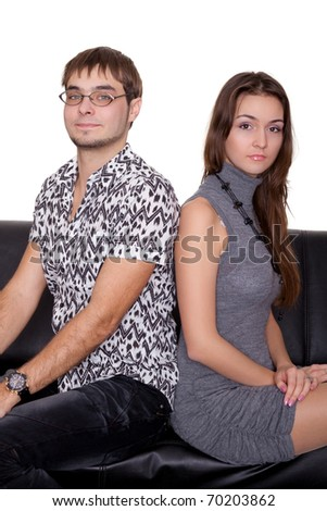 funny nerd guy and glamorous girl sitting on the sofa isolated on white - stock photo