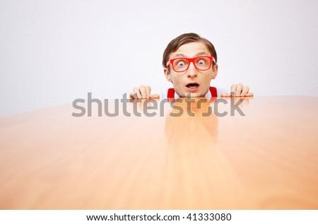 Funny nerd hiding behind a desk - stock photo