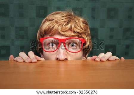 Funny nerd hiding behind a desk - stock photo