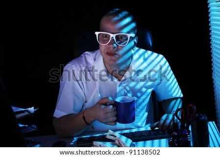 Funny nerd in glasses surfs internet at night time - stock photo