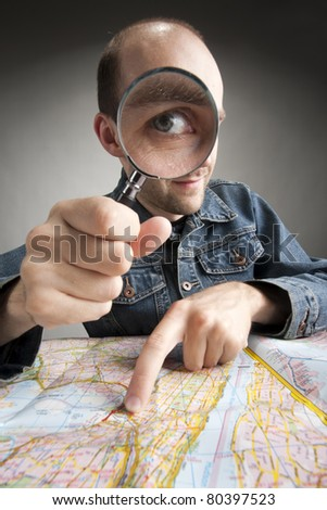Funny nerd tourist discovering map with magnifier - stock photo