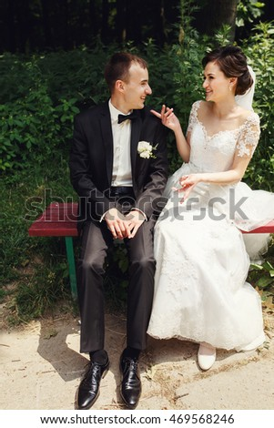Funny newlywed couple posing on red park bench