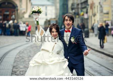 Funny newlyweds smile standing between the tram ways on the city square