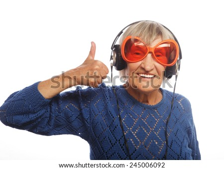 Funny old lady listening music and showing thumbs up. Isolated on white.  - stock photo