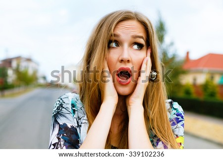 Funny outdoor portrait of crazy hipster blonde woman, put her hands to her cheeks, surprised emotions.