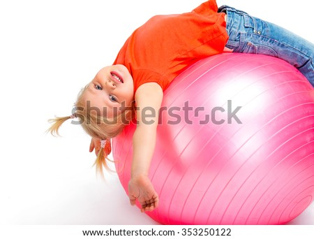 Funny photo of cute little girl lying on pink ball on white background. Girl smiling