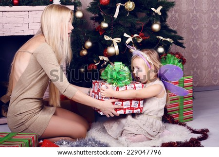 funny photo of cute little girl surprised of her big present, sitting with her mom beside a decorated Christmas tree - stock photo
