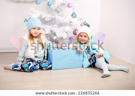 funny photo of cute little girls with blond hair wearing winter clothes posing beside a decorated Christmas tree - stock photo