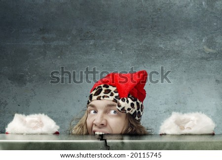 Funny photo of the afraid Santa Claus hidden under the table - stock photo