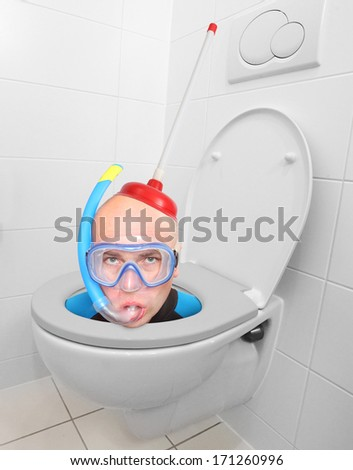 Funny picture from hotel bathroom. Crazy scuba diver in the toilet bowl. - stock photo