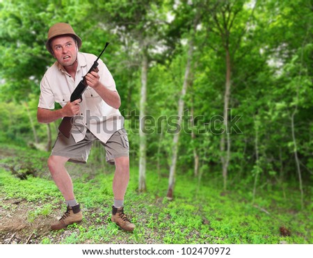 Funny picture of a crazy hunter with his hunting rifle in a tropical forest. - stock photo