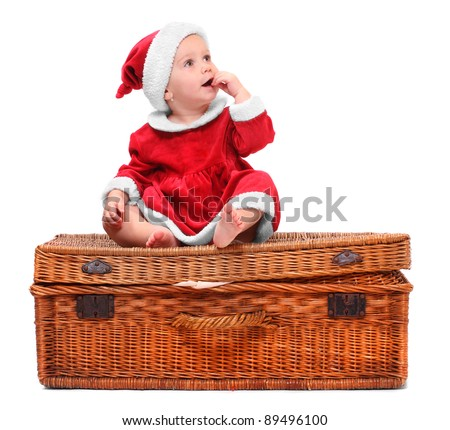 Funny picture of a little child in Santa Claus costume on a vintage gift box.