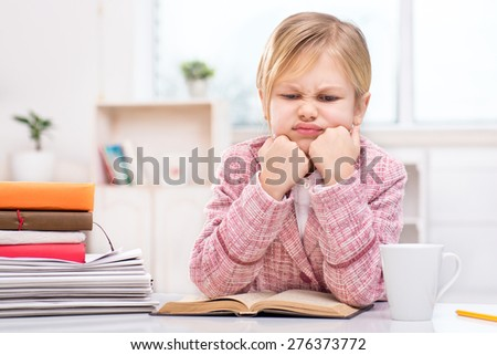 Funny picture of little cute girl playing role of business woman. Girl wearing pink suit. Girl discontentedly sitting at table with a lot of documents and notebooks. Office interior as a background - stock photo
