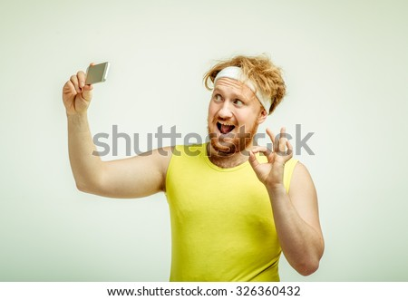 Funny picture of red haired, bearded, plump man on white background. Man wearing sportswear. Man smiling and taking a selfie  - stock photo