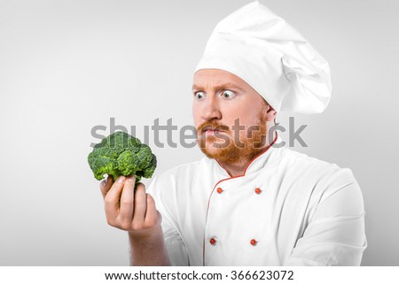 Funny picture of young male chef in white uniform. Head-cook looking at broccoli with bulging eyes - stock photo