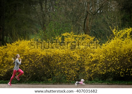 Funny picture of Young woman run in the park with dog - stock photo