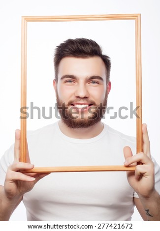 Funny picture. Young man wearing beard holding picture frame in front of his face and fun hamming, isolated on white. - stock photo