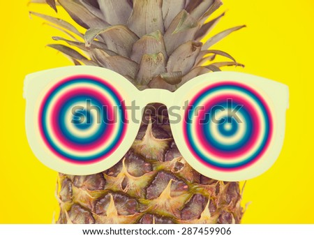 Funny pineapple in a sunglasses on yellow background - stock photo