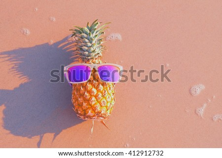 Funny pineapple in sunglasses on the beach. - stock photo