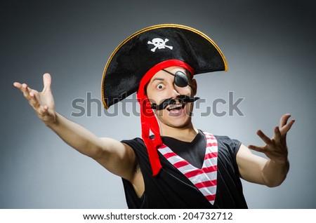 Funny pirate in the dark studio - stock photo