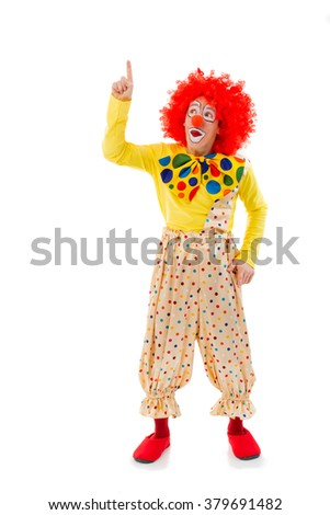 Funny playful clown in red wig pointing and looking upwards, isolated on a white background