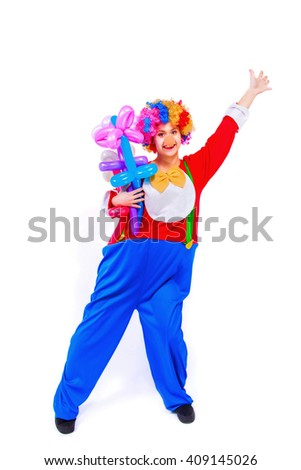 Funny playful female clown in colorful wig holding balloon flowers, like ready to fly, isolated on a white background. Clown in the costume - stock photo