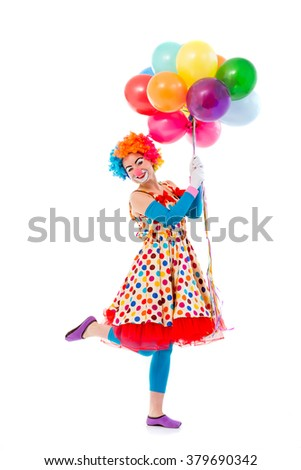 Funny playful female clown in colorful wig holding balloons, standing on one leg, looking at camera and smiling, isolated on a white background