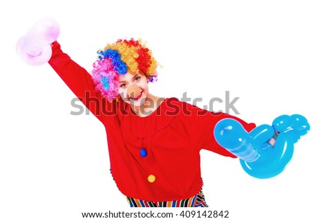 Funny playful girl clown in colorful wig holding a balloon, isolated on a white background. Clown in the costume - stock photo