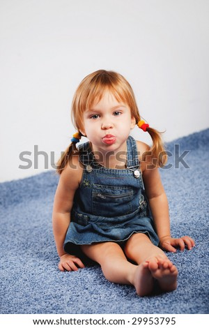 Funny playful little girl showing her tongue