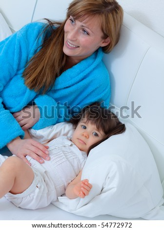Funny playful mum with baby toddler at home - stock photo