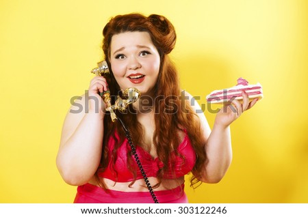 Funny plus size girl with cake and retro phone in her hands - stock photo