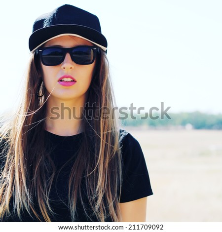 funny portrait of a beautiful girl in stylish fashion sunglasses outdoors with a retro vintage instagram filter.