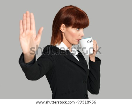 funny portrait of a beautiful, young businesswoman, drinking her morning coffee, not wanting to be disturbed, on gray background - stock photo