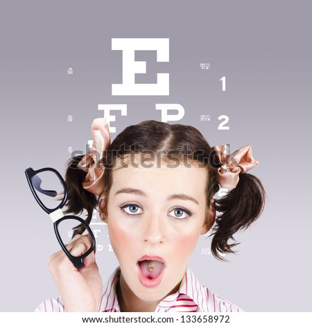 Funny portrait of a blind nerd woman holding glasses while struggling to read an optometry eyesight test chart