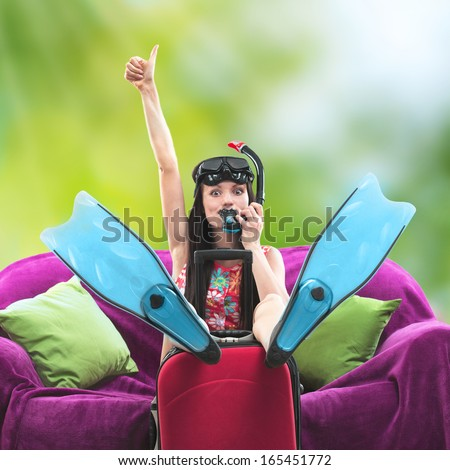 Funny portrait of a girl going on a vacation with her travel luggage and snorkeling equipment against a summer background