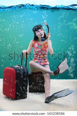 Funny portrait of a girl with her travel luggage and snorkeling equipment sitting under the sea - stock photo